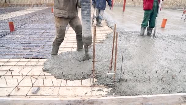 Lití betonové směsi z cement mixer na betonování bednění. Skupina zaměstnanců lití betonu na staveništi