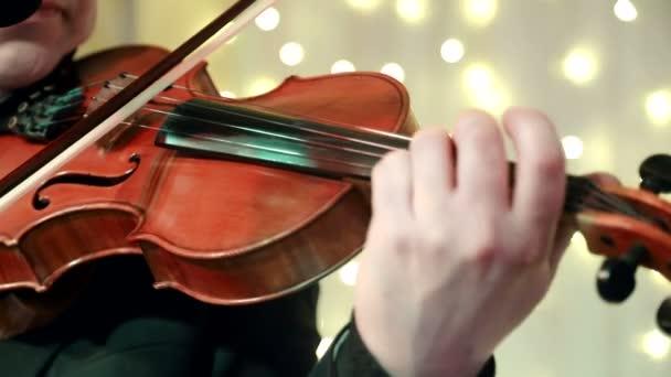 Mann Hand in Hand spielt Geige während eines Banketts in einem Restaurant