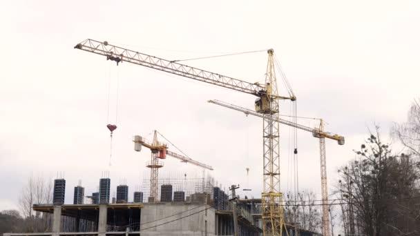 Timelapse stavební průmysl. Tři jeřáby a skupiny zaměstnanců jsou stavby domu.