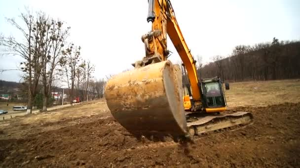 Close-up of a excavator bucket that throws out the earth. Slow motion of a digger digging a pit and throwing dirt. Shot by wide angle lens
