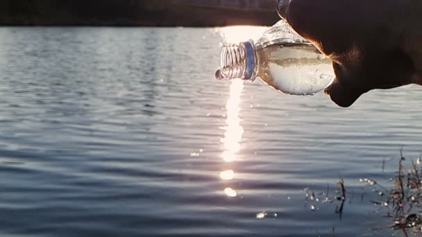 Close-up, water flows out of a plastic bottle, against the lake on a Sunny day. The sun forms a glare on the Foday. 1000FPS slow motion