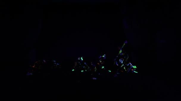 Děti v neonové světelné, dívky s fluorescenčním make-up, výtvarné návrhy ženského disco tanečnice tančí v UV světle, barevný make-up. Zpomaleně