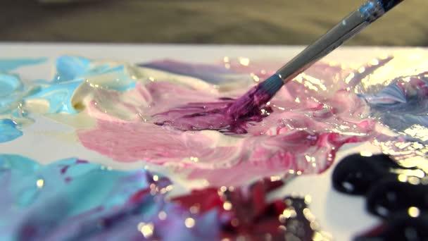 Umělec mísí různé barvy akrylové barvy štětcem pro kreslení. Příprava barev pro kreslení obrázků