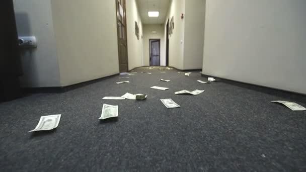 Dolarové bankovky jsou roztroušené na podlaze hotelu nebo kanceláře. Pohyby kamery na účtu
