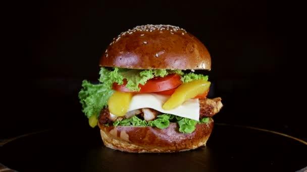 Burger s velkým kusem masa, zelení a sýr se točí na dřevěné desce na černém pozadí