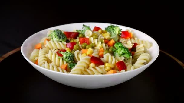 Spirálovité těstoviny se zeleninou na desce se točí na černém pozadí