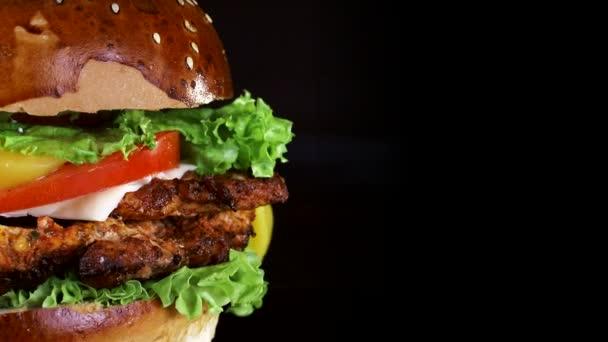 Burger zblízka s velkým kusem masa, zelení a sýrem, které se točí na dřevěné desce na černém pozadí