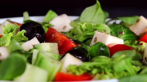 Zdravá strava. Salát ze zelených a krajíců sýrových rajčat a okurek. Otočení talíře se otáčí na černém pozadí