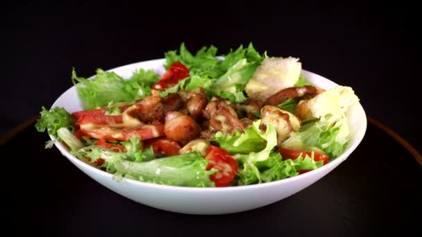 salad with greens and pieces of meat, revolves around its axis in a white plate on a black background close-up