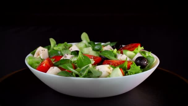 Zdravá strava. Salát ze zelených a krajíců sýrových rajčat a okurek. Deska se otáčí na černém pozadí.