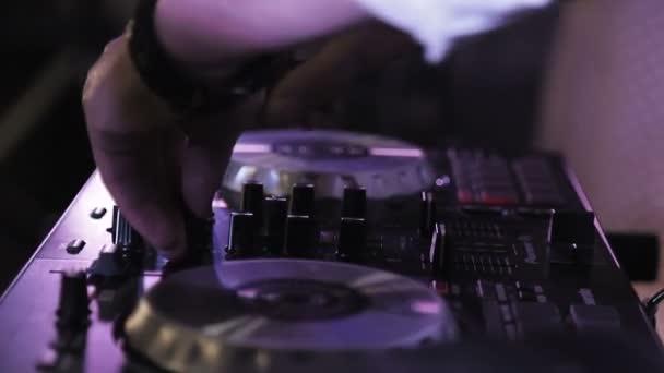 DJ játszik zene keverés és karcolás a lemezjátszó zenei felszerelések. Lámpával és kezelővel ellátott professzionális zenei felszerelések.