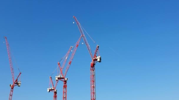 Drei Baukräne in roter Farbe, die dicht am blauen wolkenlosen Himmel stehen. die Aussicht vom Ausflugsboot