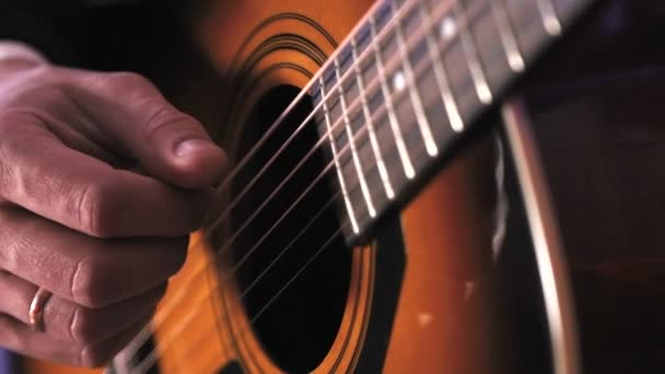 A man plays an acoustic guitar. Close-up of the hand that hits the strings of the guitar