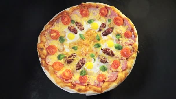 Top view delicious pizza, which rotates natals. Pizza with sausage, tomatoes and mushrooms.