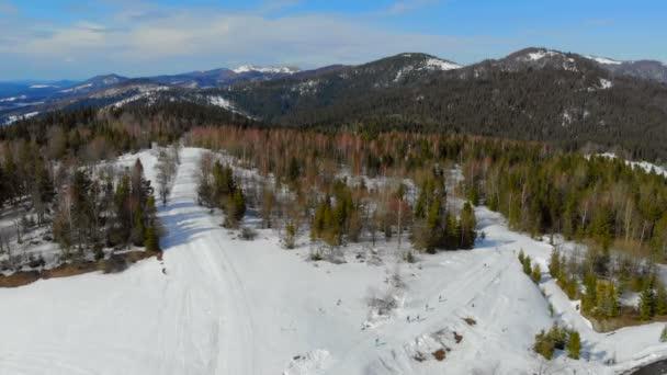 Letecký pohled na závod mezi sportovci v horách. Biatlon v zimních horách. Skupina sportovců překonává vzdálenost.