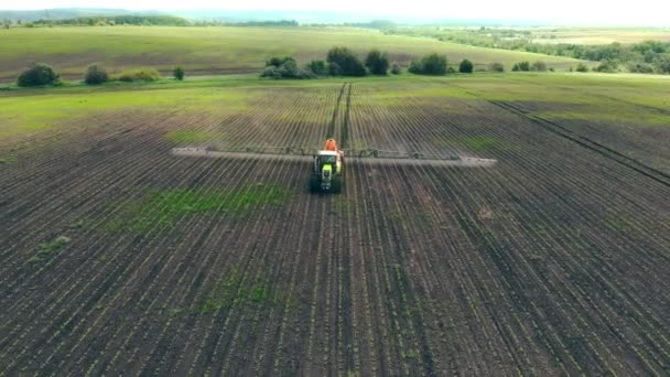 Aerial view Farm machinery spraying insecticide to the green field, agricultural natural seasonal spring works. Farming tractor spraying on field with sprayer