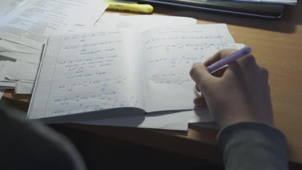 Muž řeší matematické problémy v notebooku a připravuje se na trénink. Muž píše s perem vzorec v zápisníku zblízka.