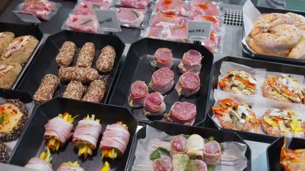Chuťové masné výrobky jsou vystaveny ve speciálních nádobách. Masné výrobky na prodej v okně supermarketu.