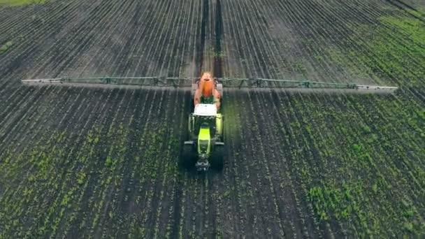 Letecký výhled Zemědělské stroje rozprašující insekticid na zelené pole, zemědělské přírodní sezónní jarní práce. Farming tractor spraying on field with sprayer