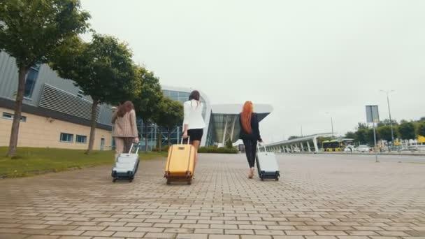 Három boldog lány megy nyaralni, és megy a reptérre csomagokkal a kezükben. Tourist Pihenés vagy utazás a nők férfiak nélkül.