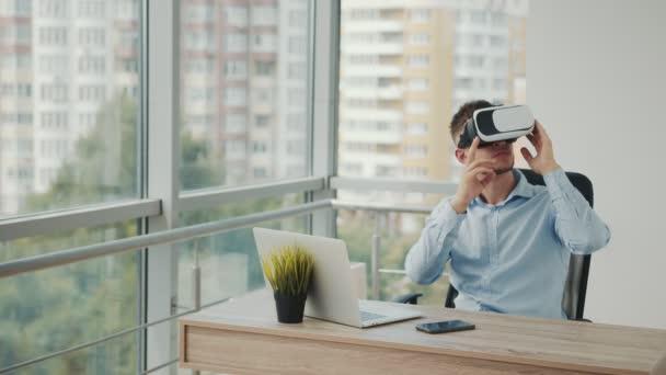 Ein junger Mann sitzt an einem Schreibtisch im Büro und arbeitet mit einer Augmented-Reality-Brille an Geschäftsprojekten in verschiedenen Bereichen.