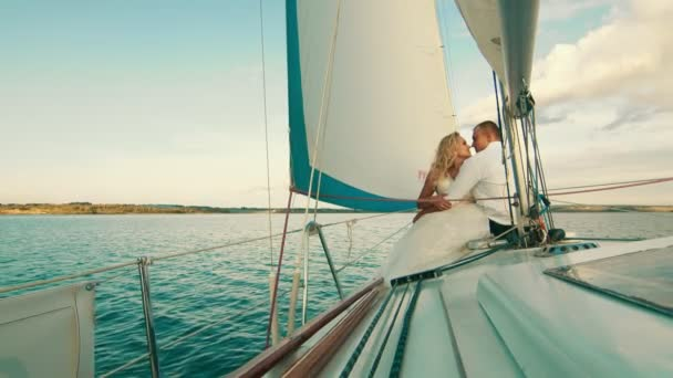 The newlyweds are sailing on the lake aboard the yacht. They enjoy each other, look and smile. Touching each others noses
