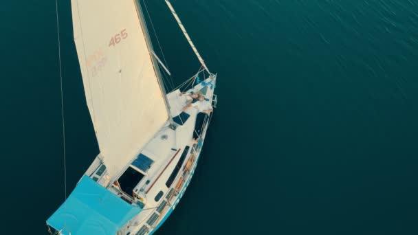 Ukrajina. Lvove. 19.09.2020. Jedna jachta v moři z ptačí perspektivy při západu slunce. Obloha se odráží ve vodě. Let při západu slunce v blízkosti jachty s výhledem na plachtu z výšky