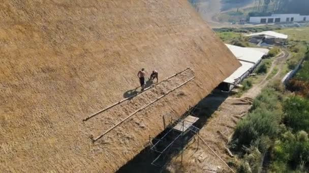 Aerial view the roof of a large house with dry straw and hay. Workers who install the roof.