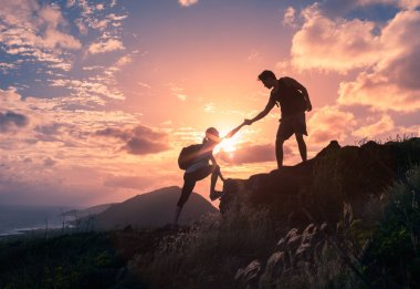 People helping each other hike up a mountain at sunrise.