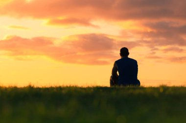 oung man sitting outdoors watching the sunset. Thinking and relaxing concept.