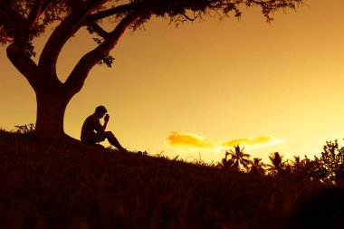 Silhouette of depressed man sitting under the tree.