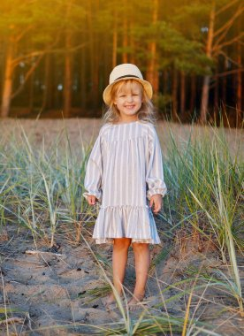 Little caucasian girl in dress and hat walking in the beach outdoor, summer time, sunlight, happy emotions, freedom concept