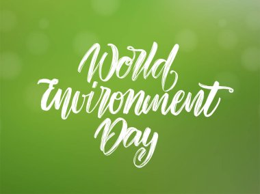 Handwritten type lettering composition of World Environment Day on green blurred nature background