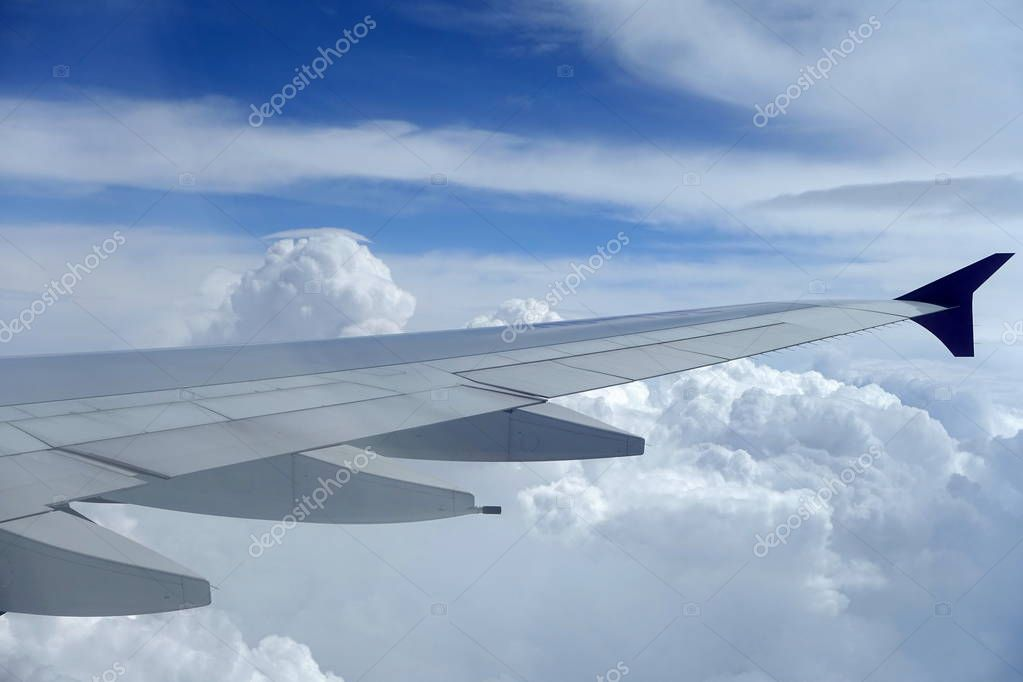 View of an Airplane Wing against a Blue Cloudy Sky