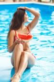 Nagyon szép nő görögdinnyével a medencében.