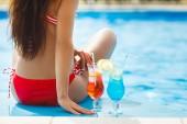 sehr schöne junge Frau mit Cocktails im Schwimmbad