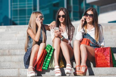 Young pretty girls making selfie and having fun outdoors. Women talking on a mobile phone