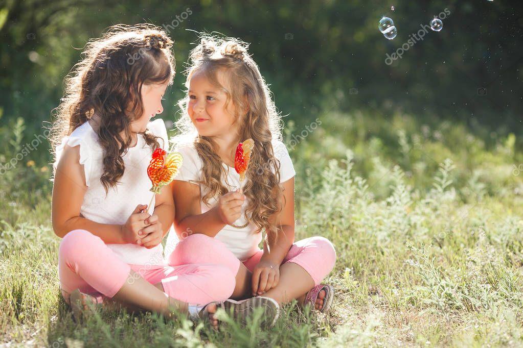Cute little girls friends having fun together outdoors,
