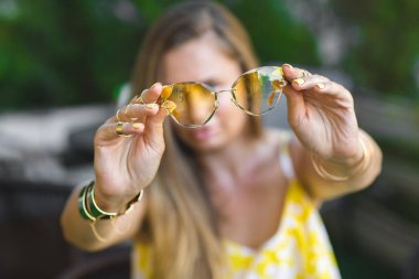 Young woman holding yellow sunglasses in her hands in front of camera. Still of stylish accessories