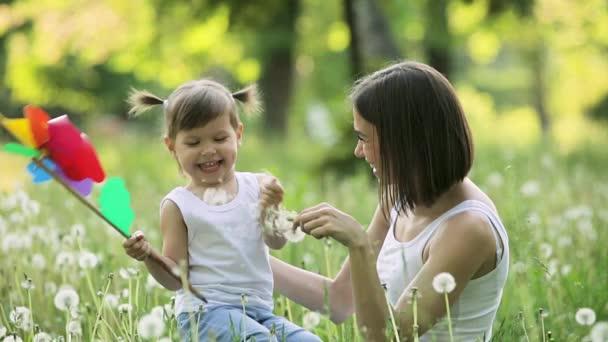 Mladá šťastná matka a její dcera si hrají na louce s pampeliškami. Šťastná rodina venku. Žena a její dítě spolu na letním pozadí.