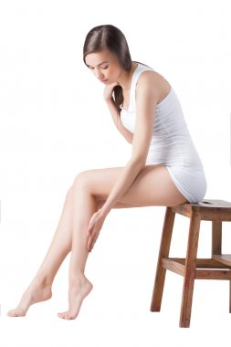 Young woman on isolated white background. Women`s legs studio shot.
