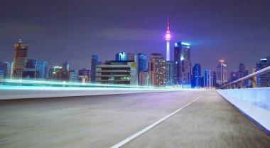 Moving forward motion blur asphalt road on night scene near the modern city.