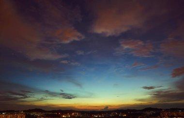Beautiful panorama natural sunset sunrise over silhouettes city skyline and amazing orange cloud blue sky above it .