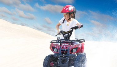 Little girl riding ATV quad bike in desert with beautiful blue and white sky .