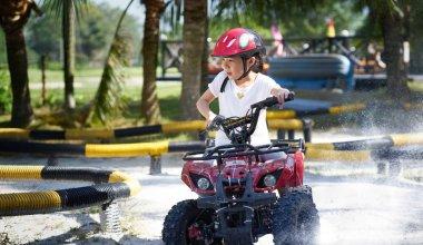 Little girl riding ATV quad bike in race track .