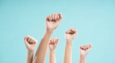 Multiethnic male and female hands raised against a blue background