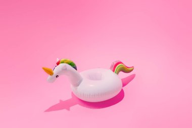 Inflatable unicorn pool toy on pastel pink background, Minimal summer concept