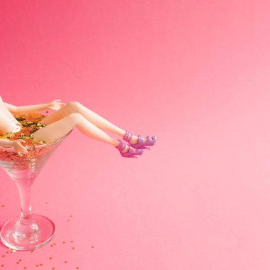 female doll bathing in martini glass full of golden glitter on pink background, Creative minimal beauty summer concept