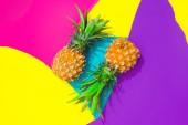 Kreatív trópusi elrendezés ananásszal, színes élénk papírok. Elvont színek képzőművészeti háttérrel. Minimális nyári koncepció. Lapos feküdt.