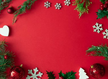 Red Christmas background with winter decorations and tree branches and leaves. Holiday copy space layout.